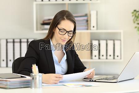 office worker wearing eyeglasses reading a