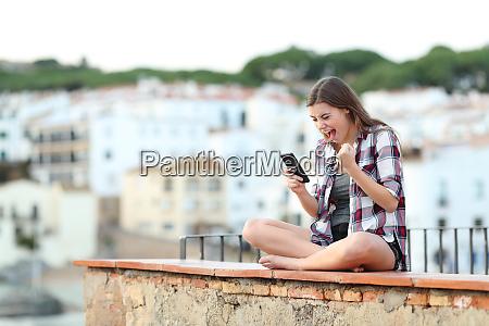 excited teenage girl reading online phone