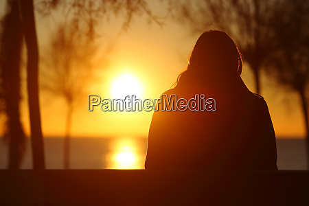 silhouette of a lonely woman watching