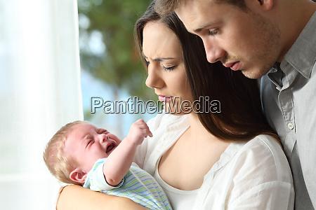 muede verzweifelte eltern und baby weinen