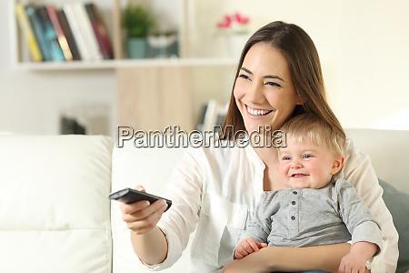 glueckliche mutter und baby beim fernsehen
