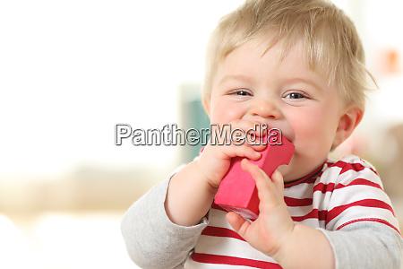 froehliches baby beissen ein spielzeug und
