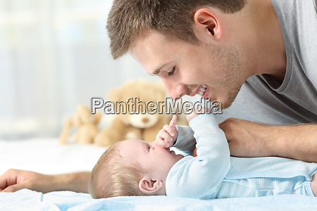 baby playing with his father