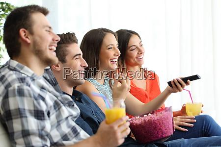 glueckliche freunde die zu hause fernsehen