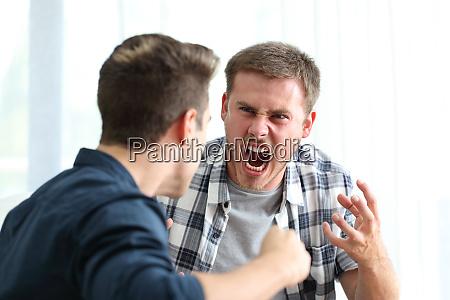 zwei wuetende maenner streiten und bedrohen
