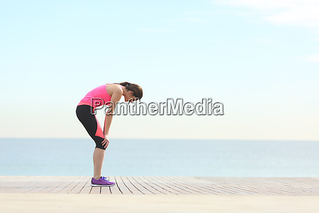 exhausted runner resting on the beach