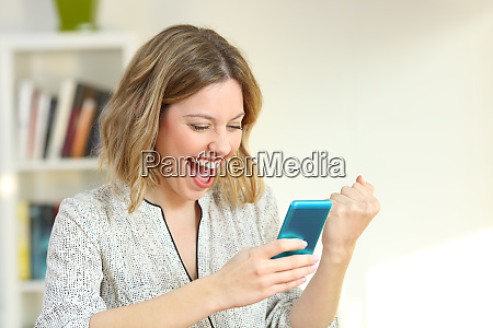 excited woman reading smart phone content