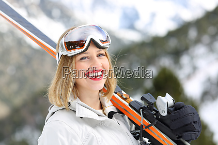 happy skier looking at camera holding