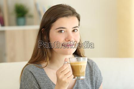 gluecklich teen haelt einen kaffee mit