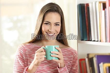 glueckliche frau haelt eine kaffeetasse schaut