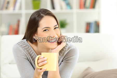happy woman posing holding a coffee