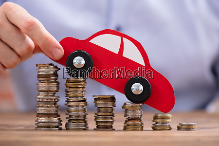 person holding car over declining stacked