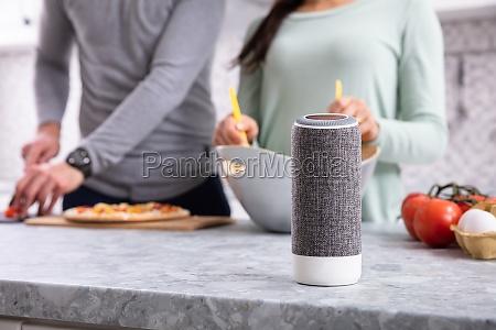 couple preparing food behind wireless speaker