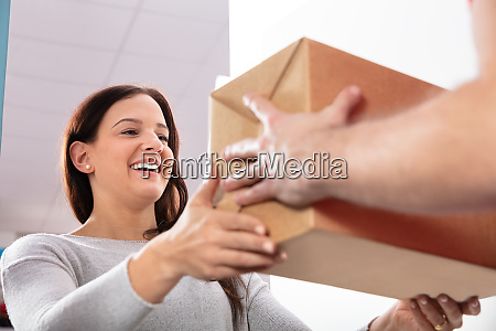 delivery man giving box to young