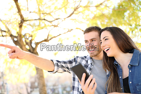 happy couple holding phone pointing location