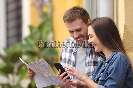 happy couple of tourists checking phone
