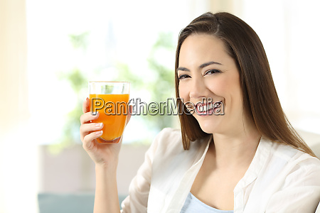 woman holding a glass of orange