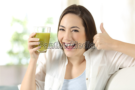 woman holding a vegetable juice with