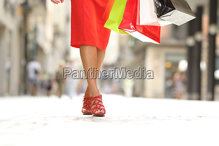 beauty woman legs walking holding shopping