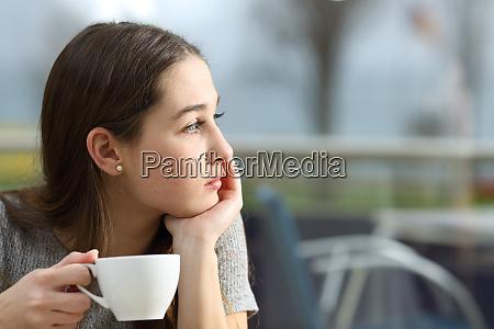 umfassende frau schaut in einem cafe