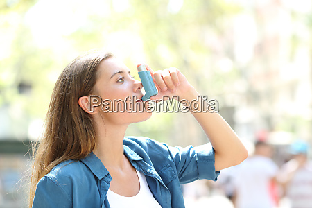 asthmatic woman using a inhaler outdoors