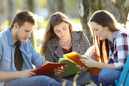 three students studying memorizing notes