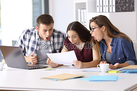 amazed employees reading a document at