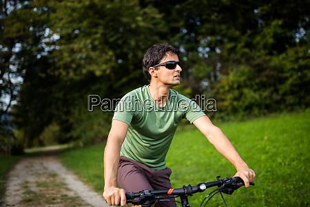 junger mann faehrt mit seinem mountainbike