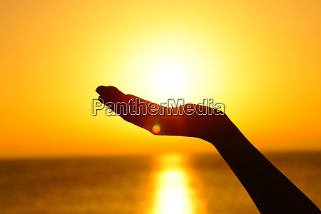 woman hand holding sun at sunset