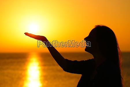 woman profile holding sun at sunrise