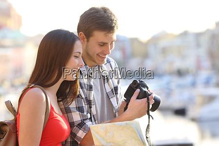 couple of tourists checking photos on