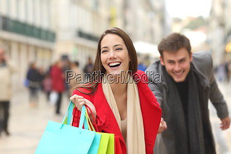 couple of shoppers running with shopping