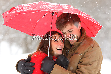 romantic couple hugging under umbrella snowing