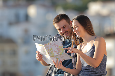 happy tourists checking guide in a