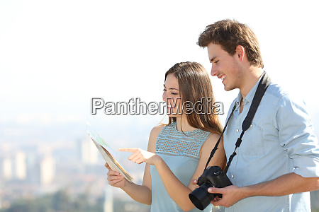 happy tourists checking paper guide on