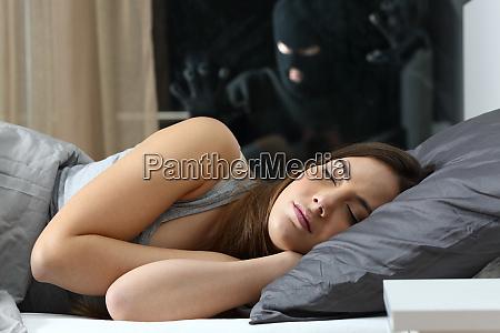 woman sleeping with an intruder watching