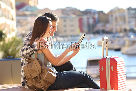 couple of tourists consulting a tablet