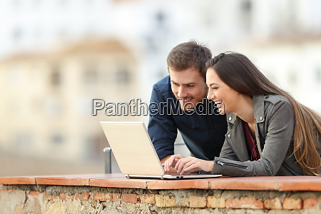 happy couple searching online content on