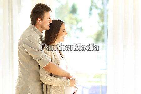 pregnant woman and husband looking trough