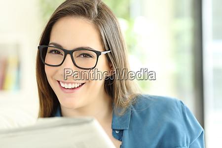 frau haelt eine zeitung mit brille