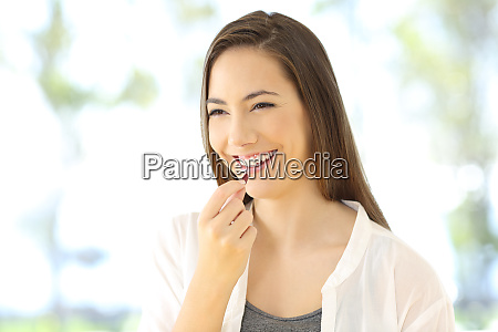 woman taking a pill looking away