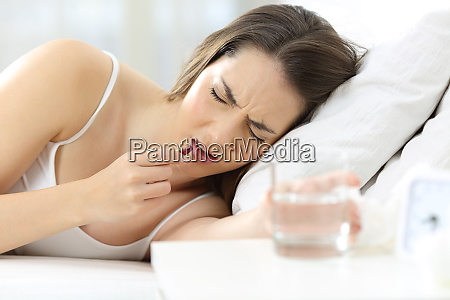 ill woman taking pill lying on