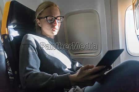 woman wearing glasses reading on digital