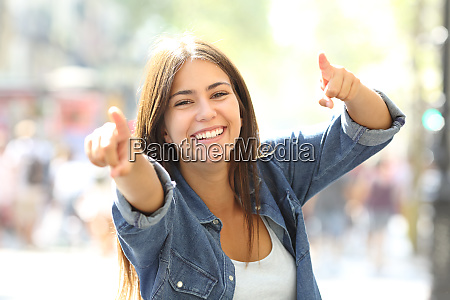 joyful girl pointing at camera in