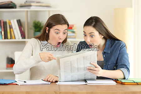 two amazed students reading a newspaper