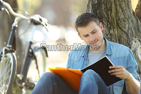 student studiert lesenotizen im freien