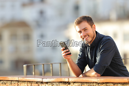 happy man holding a phone looking