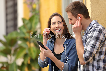 happy couple sharing music in a