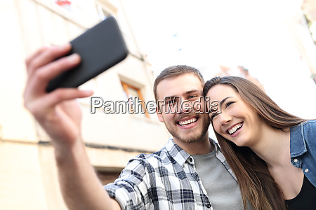 happy couple taking selfies with smartphone
