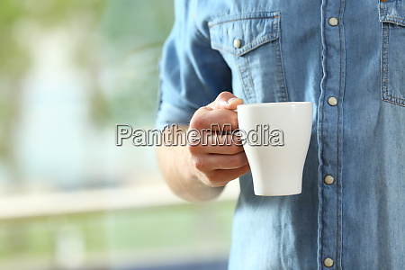 hand des mannes haelt eine kaffeetasse